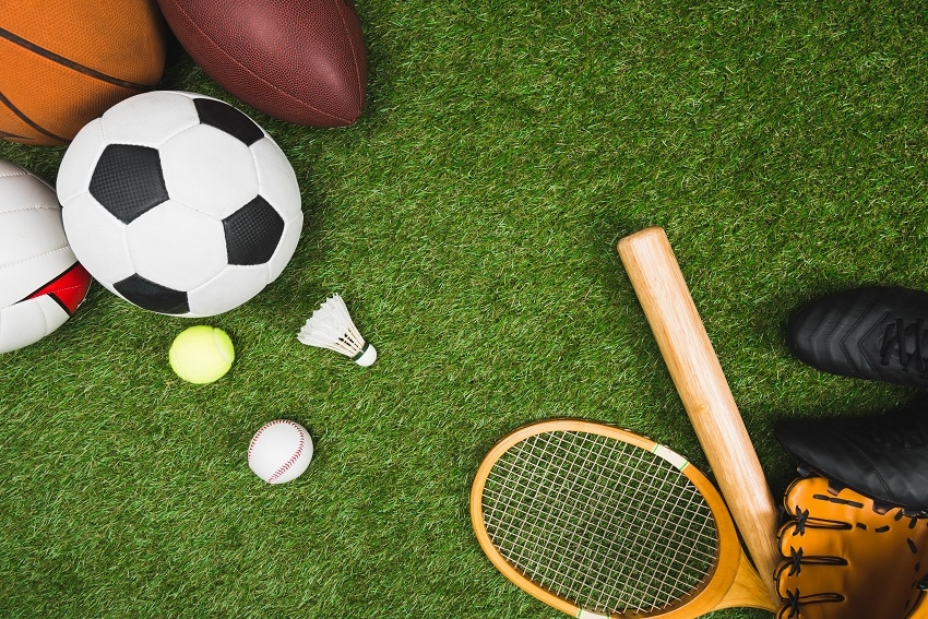 top view of various sport balls, baseball bat and glove, badminton racket on green lawn – โปรโมชั่น แจกเครดิตฟรี